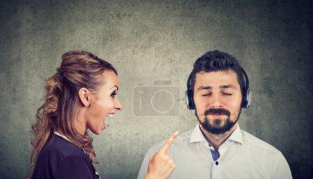 Photo pour Femme en colère criant sur un mari calme en écoutant de la musique avec des écouteurs - image libre de droit