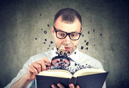 Photo pour Homme étonnant utilisant loupe lecture d'un livre avec des lettres s'envolant loin de lui - image libre de droit