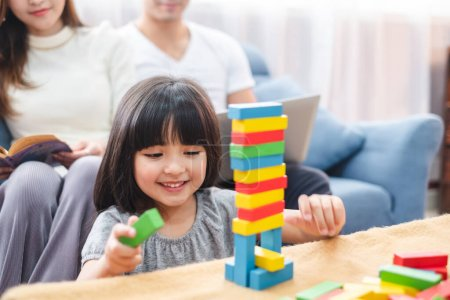 Photo for Girl daughter playing blocks toy over father and mother, happy family concept - Royalty Free Image