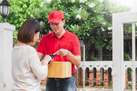 Photo pour Livreur asiatique livrer boîte colis paquet au client à la maison, expédition concept de livraison - image libre de droit