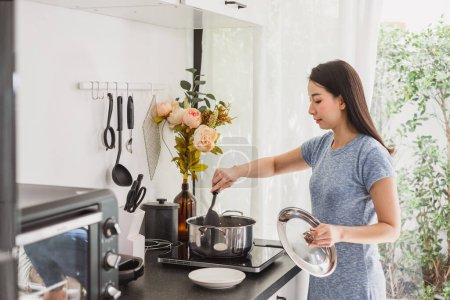 Photo for Young Asian woman making healthy food  in kitchen at home - Royalty Free Image