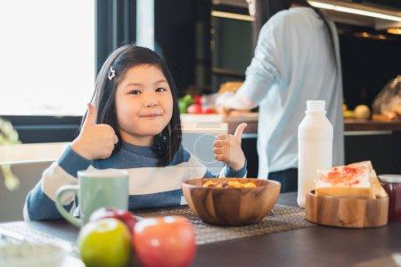 Photo pour Asiatique fille enfant avoir petit déjeuner céréales à la maison cuisine - image libre de droit