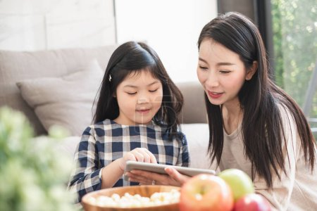Photo for Happy Asian family using tablet, laptop for playing game watching movies, relaxing at home for lifestyle concept - Royalty Free Image