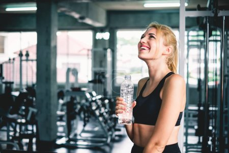 Photo pour Femme boire de l'eau après avoir terminé l'entraînement à la salle de sport, avec sourire heureux et se détendre - image libre de droit