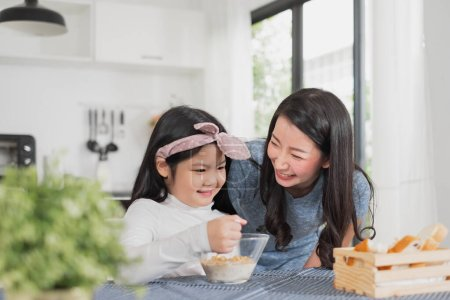 Photo for Asian family happy enjoy having breakfast on table in kitchen - Royalty Free Image