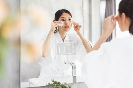 Photo pour Asian woman cleaning face front of mirror, skin care and cosmeti - image libre de droit