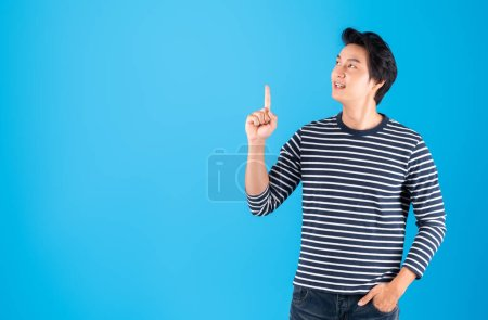 Photo for Young handsome Asian man / happy guy pointing to above copy space isolated over blue background, studio shot - Royalty Free Image