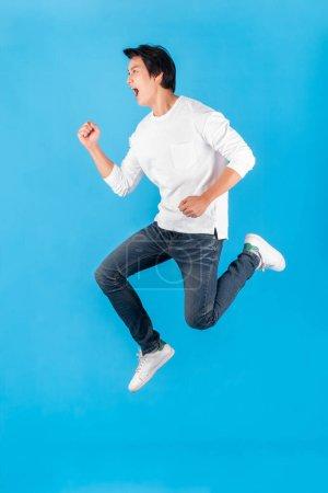 Photo pour Jeune homme asiatique sautant avec heureux et excité sur fond bleu - image libre de droit