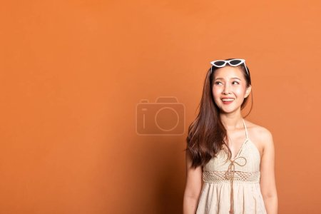 Photo for Young Asian woman in summer swimming suit smile happy over orange background with copy space - Royalty Free Image