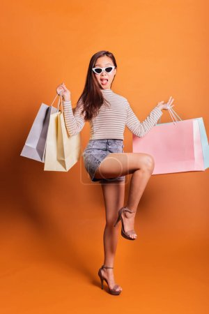Photo for Young beautiful fashionable Asian woman holding shopping bags phone and credit card over orange background studio shot - Royalty Free Image