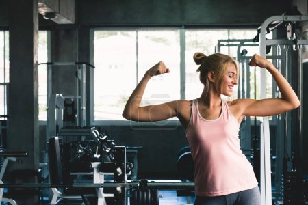 Photo pour Femme forte posant à la musculation sportive de gymnase avec un sourire heureux sentiment, concept d'entraînement de gymnase - image libre de droit