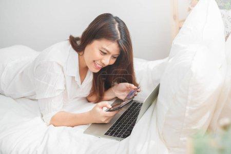 Photo pour Belle femme asiatique utilisant ordinateur portable et téléphone intelligent dans la chambre à coucher pour les achats en ligne, concept de style de vie femme asiatique - image libre de droit