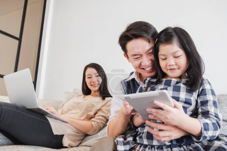 Photo for Happy Asian family spending time together at home playing game, tablet for education - Royalty Free Image