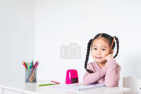Photo for Asian girl kid doing drawing with many colour pencils on white paper over white background - Royalty Free Image