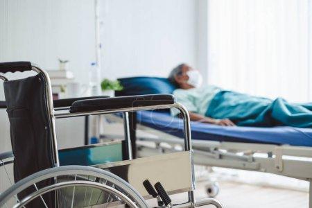 Photo pour Gros plan fauteuil roulant sur vieux patient handicapé avec masque à l'hôpital - image libre de droit