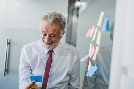 Photo pour Old senior business man happy working in office, reading sticky note post it in room - image libre de droit