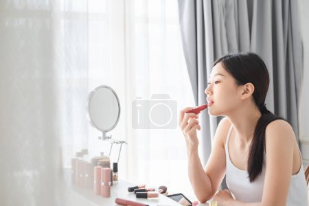 Photo pour Young beautiful Asian woman applying cosmetics make up on her face, health beauty skin care and make up concept - image libre de droit