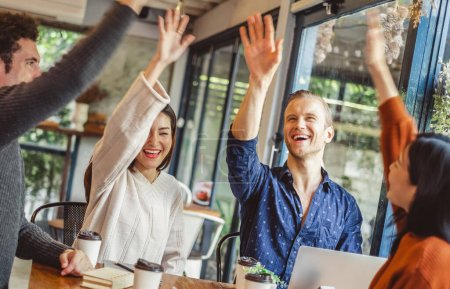 Photo pour Business people smile and raise hands up, feeling happy , complete finish job, teamwork successful/achievement working in cafe concept - image libre de droit