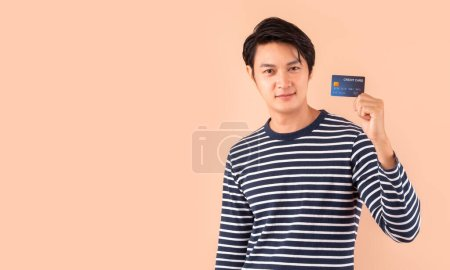 Photo for Young Asian man holding credit card over pink background with copy space, credit card payment for cashless online shopping concept - Royalty Free Image