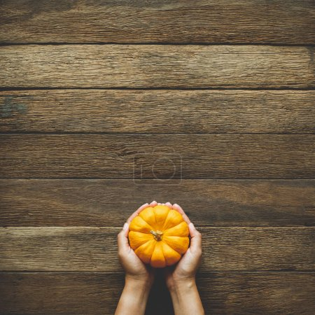 Photo for Thanksgiving background, human hand holding pumpkin over wood table background with copy space. flatlay - Royalty Free Image
