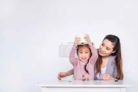 Photo for Happy Asian family inserting coins to box over white background for saving money concept - Royalty Free Image