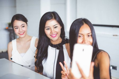 Photo pour Asiatique femme d'affaires prendre des photos en faisant selfie pendant le travail dans le bureau - image libre de droit
