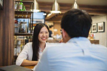 Photo pour Jeune belle femme d'affaires asiatique dans un café, discuter des affaires pendant l'entrevue avec un jeune homme d'affaires - image libre de droit