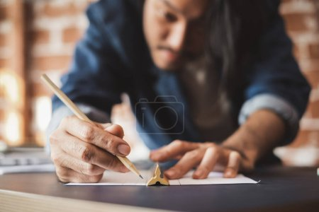 Photo pour Young Asian man draft a drawing plan for artwork, architect, engineering drawing, creative designer concept - image libre de droit