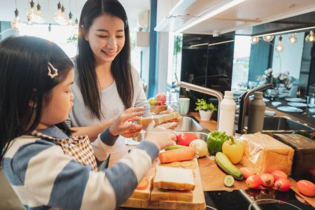 Photo for Asian Mother and her daughter kid cooking food for breakfast in kitchen - Royalty Free Image