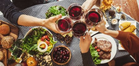 Photo for Group of young people celebrating Christmas thanksgiving party dinner with clinking glass of wine, top view - Royalty Free Image