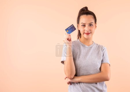 Photo for Young Asian woman holding credit card over pink background with copy space, credit card payment for cashless online shopping concept - Royalty Free Image