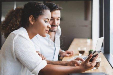 Photo pour Jeune homme et femme travaillant sur ordinateur portable et utilisant le téléphone mobile se détendre dans le bureau d'affaires - image libre de droit