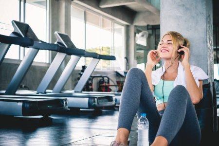 Photo pour Femme écoutant de la musique pendant l'entraînement et se reposer au gymnase sportif pour se détendre avec bonheur et sourire - image libre de droit