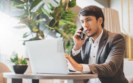 Photo pour Asiatique homme d'affaires en utilisant ordinateur portable et téléphone mobile tout en travaillant dans le bureau - image libre de droit