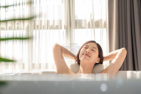 Photo pour Young beautiful Asian woman taking bath in  bathtub, massaging perfect skincare - image libre de droit