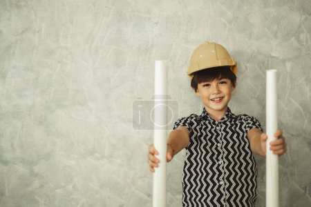 Photo for Kid, boy, child engineer, holding blueprint, drawing with safety helmet and copy space - Royalty Free Image