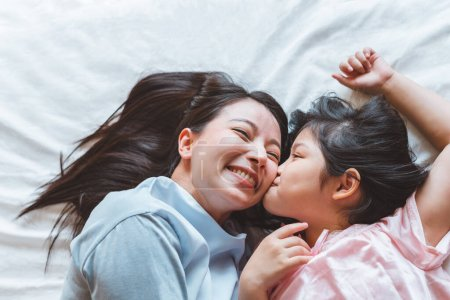 Photo for Asian mother kissing daughter in bedroom, with love and warm family concept - Royalty Free Image