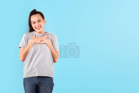 Photo for Portrait happy Asian woman, cute girl smile hands touch on chest over blue background with copy space, satisfied and impressive concept - Royalty Free Image
