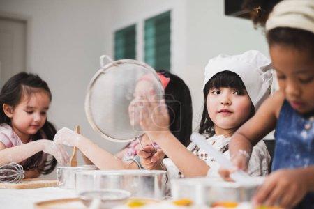 Photo pour Groupe diversité enfants fille faire gâteau boulangerie dans la cuisine - image libre de droit