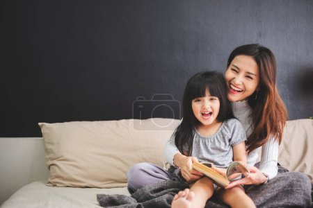Photo for Happy Asian family mother and daughter on bed in bedroom say good night before sleep - Royalty Free Image