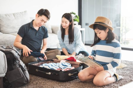 Photo for Asian family packing bag/luggage and planning to travel on summer vacation - Royalty Free Image
