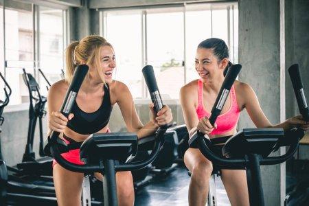 Photo pour Entraînement de femme au gymnase de sport par vélo de machine pour le cardio, concept d'entraînement de gymnase - image libre de droit