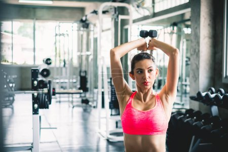Photo for Woman workout by lifting dumbbell for weight training at sport gym - Royalty Free Image