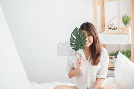 Photo pour Portrait beau style de vie de femme asiatique avec feuille verte dans la chambre à coucher - image libre de droit