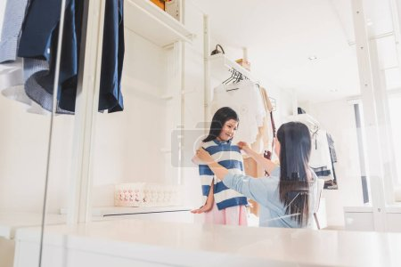 Photo for Asian mother dressing/choosing clothes to her girl daughter from wardrobe in bedroom, Asian family lifestyle concept - Royalty Free Image