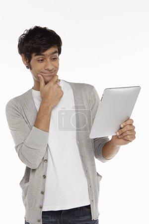 Photo pour Homme avec tablette numérique, contemplant - image libre de droit