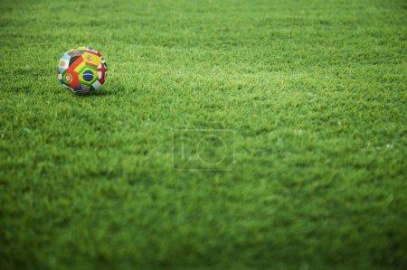 Photo pour Un ballon de football des drapeaux du monde sur le terrain de jeu - image libre de droit