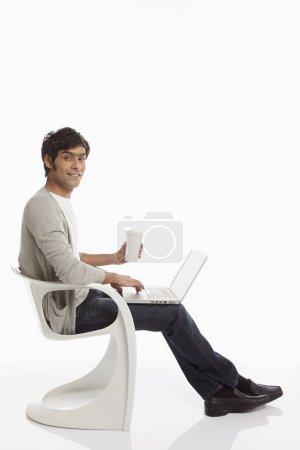 Photo pour Homme prenant un verre tout en utilisant un ordinateur portable - image libre de droit