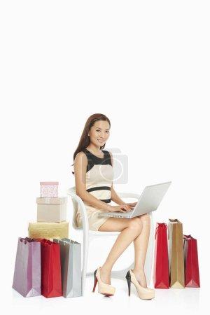 Photo pour Femme utilisant un ordinateur portable tout en étant assis - image libre de droit