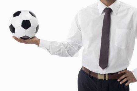Photo pour Directeur de football tenant un ballon avec une main - image libre de droit